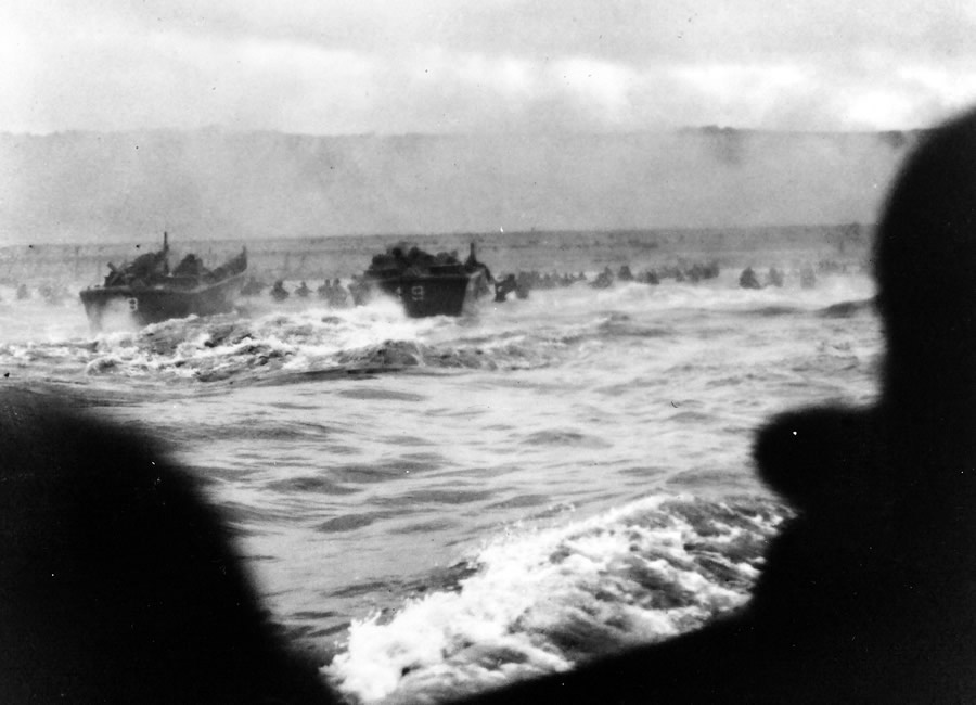 Original caption: June 6, 1944 — Coast Guard Barges Hit the French Coast- Coast Guard landing barges hit the French Coast with the first wave of American troops under heavy fire from Nazi beach nests. This photo, taken from a landing barge by a Coast Guard combat photographer, shows the troops waist deep as they wade ashore. These landing barges shuttled back and forth from their assault transports to the beach carrying troops throughout D-Day.