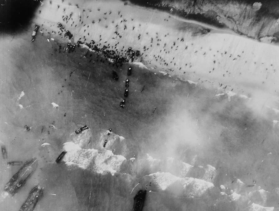Original caption: Men and assault vehicles storm the beaches of Normandy as allied landing craft make a dent in Germany's West Wall on June 6, 1944. As wave after wave of landing craft unload their cargo, men move inland and vehicles surge up the roads. Note the men swarming over the beaches.