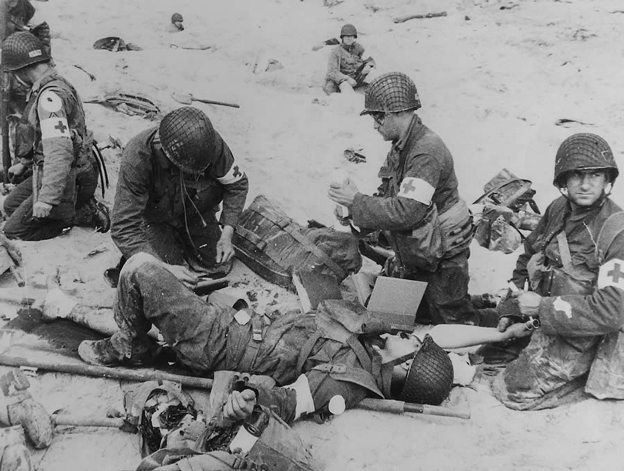 Original Caption: American Medics render first aid to troops in the initial landing on Utah Beach. Les Dunes de Madeleine, Northern Coast, France. In the background other members of the landing parties dig into the soft sand of the beach. June 6, 1944.