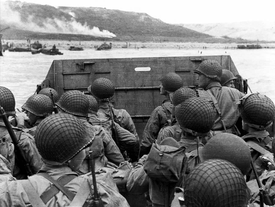 American assault troops in a landing craft huddle behind the protective front of the craft as it nears a beachhead, on the Northern Coast of France. Smoke in the background is Naval gunfire supporting the land. June 6, 1944.