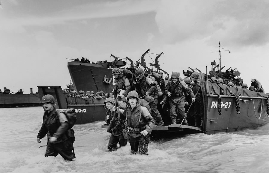 Original caption: It's Their Turn Now — American reinforcements, eager for their shot at the retreating Nazis in Normandy, pile from a Coast Guard landing barge into the surf on the French coast. Hardened for battle, they are going in to reinforce and replace the fighting units that secured the Norman beachhead and spread north toward Cherbourg.
