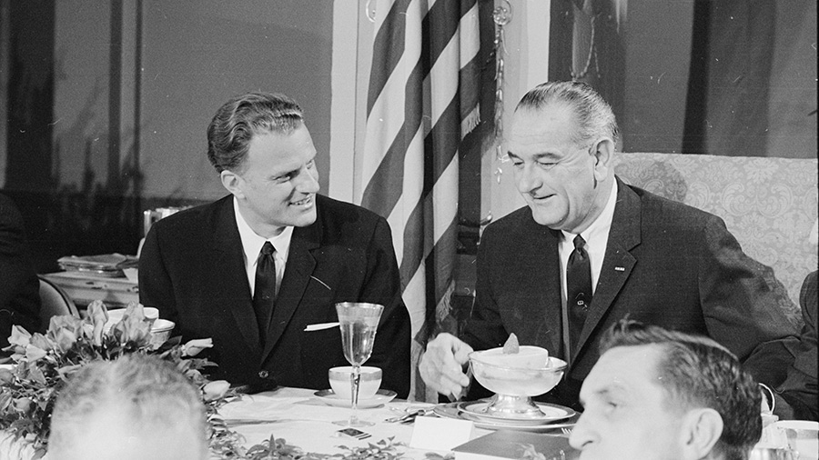 American evangelist Billy Graham and US President Lyndon B Johnson talk together at the Annual Presidential Prayer Breakfast, Washington DC, February 5, 1964.