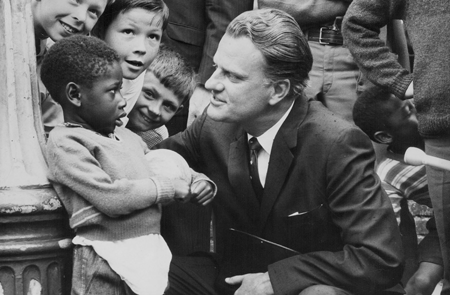 Billy Graham talking to a group of children during a visit to Brixton Parish Church, London, June 12th 1966.