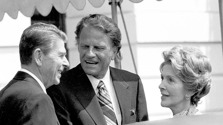 The Reverend Billy Graham talks with President Ronald Reagan and first lady Nancy Reagan at the White House July 18, 1981.