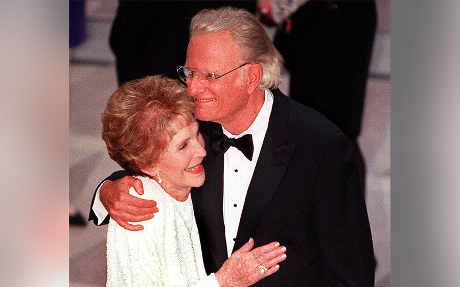 Former US First Lady Nancy Reagan and Reverend Billy Graham embrace during the gala dedication of the Ronald Reagan Building and International Trade Center 05 May in Washinghton, DC.