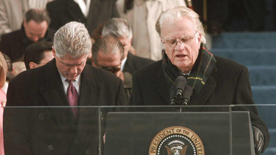 US President Bill Clinton bows his head as Reverend Billy Graham gives the invocation at the beginning of the inaugural ceremony 20 January on Capitol Hill in Washington, DC.