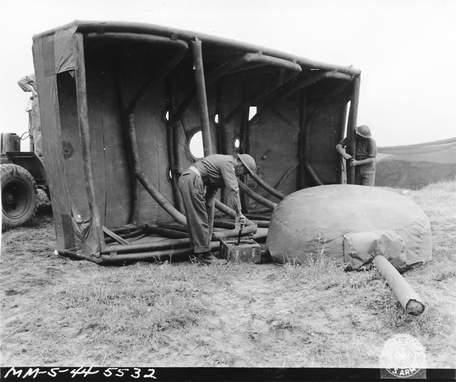 5/20/1944 — Original caption: Fifth Army. Anzio Area, Italy. Dummy tank designed by British, made of rubber and inflated when used. Can be assembled in 20 minutes. When used in field can simulate tank positions. Inflating the turret assembly with the forge pump. In the background can be seen the fully-inflated body assembly with is resting on its side in order to show the air-tube supporting framework. Photo by: Gallagher