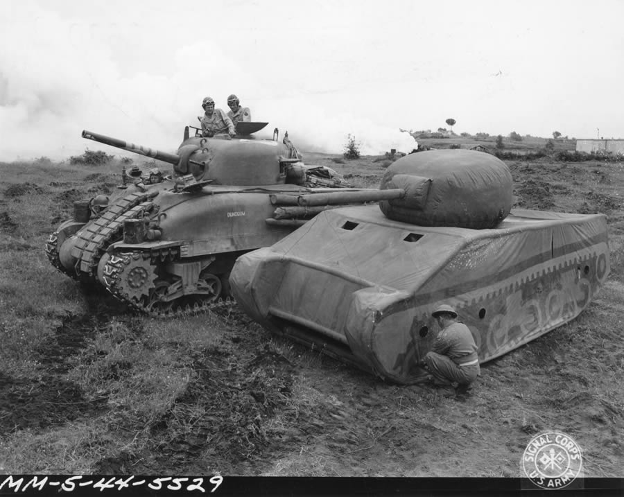 5/20/1944 — Original Caption: Dummy tank designed by British, made of rubber and inflated when used, can be assembled in 20 minutes. When used in field can simulate tank positions. Comparison between United States Army medium tank, Mark IV, and the completely inflated and assembled dummy which is slightly smaller. Photo by Gallagher, 163rd Signal Photo Company