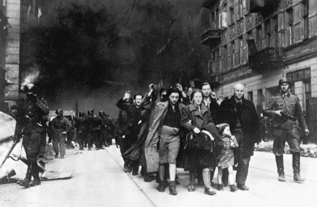 Captured Jews are led by German troops to the assembly point for deportation. Warsaw, Poland 1943