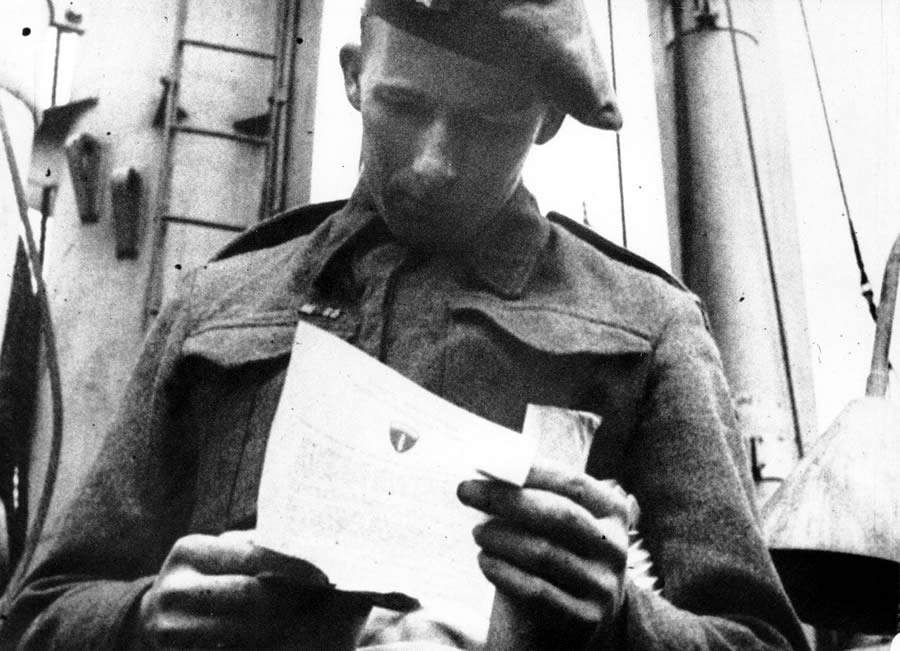 June 6, 1944 — British soldier aboard ship reading General Eisenhower's Order of the Day on the way to Normandy, France.