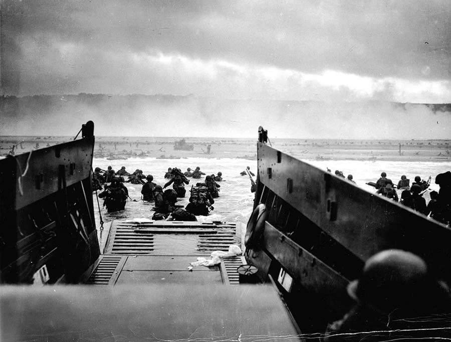 Original Caption: June 6, 1944 — Down the ramp of a Coast Guard Landing barge Yankee soldiers storm toward the beach-sweeping fire of Nazi defenders in the D-Day Invasion of the French Coast. Troops ahead may be seen lying flat under the deadly machine gun resistance of the Germans. Soon the Nazis were driven back under the overwhelming Invasion forces thrown in from Coast Guard and Navy amphibious craft.