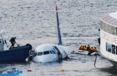 """FILE - In this Jan. 15, 2009 file photo, a diver, left, aboard an NYPD vessel prepares to rescue passengers that escaped from the Airbus 320 US Airways aircraft made an emergency landing in the Hudson River in New York in what came to be known as the """"Miracle on the Hudson"""" because everyone survived. It's been 10 years since US Airways flight 1549 landed on the Hudson River after colliding with a flock of geese just after takeoff."""