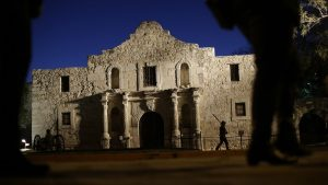 """In this March 6, 2013 file photo, Dan Phillips, a member of the San Antonio Living History Association, patrols the Alamo during a pre-dawn memorial ceremony to remember the 1836 Battle of the Alamo and those who fell on both sides, in San Antonio. Texas Land Commissioner George P. Bush is overseeing a 7-year, $450 million revamp of the Alamo, where 189 independence fighters were killed in 1836. That includes restoration of historical structures and building a new museum and visitors' center. But some conservatives worry that the importance of the battle for the Alamo will be marginalized by """"political correctness,"""" with the overhaul sanitizing less-desirable aspects of participants' history, including that some were slaveholders."""