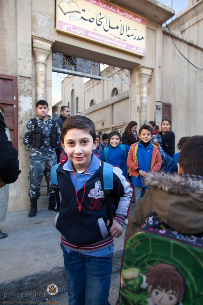 A member of the Sootoro is seen in the background providing protection for the students as they leave school. The Picture Christians Project/Jeff Gardner