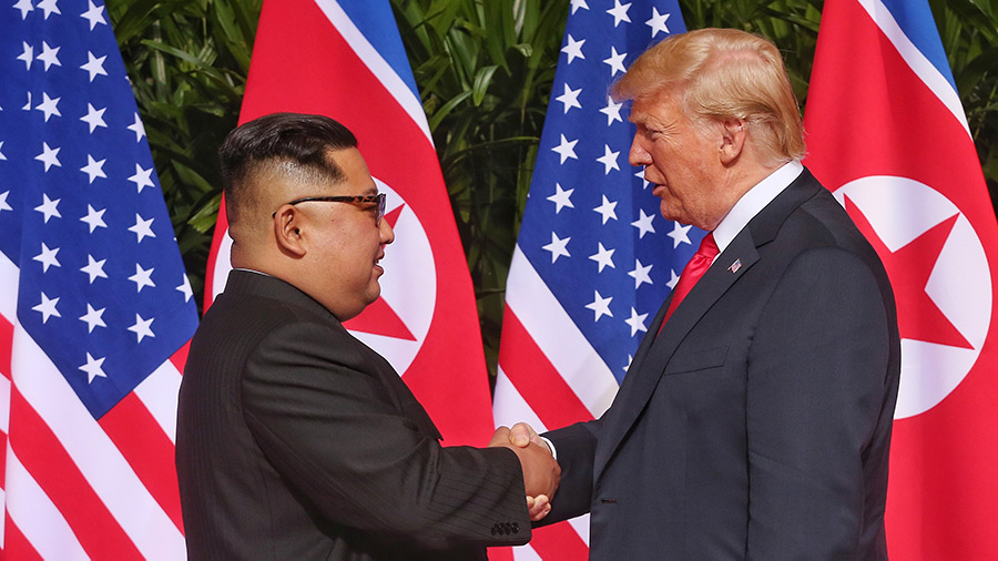 North Korean leader Kim Jong-un (L) shakes hands with U.S. President Donald Trump during their historic U.S.-DPRK summit at the Capella Hotel on Sentosa island on June 12, 2018 in Singapore.