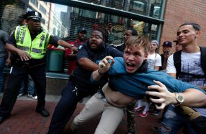 "A counterprotester, part of a small group who remained on the street hours after a ""Free Speech"" rally was staged by conservative activists, scuffles with a security guard and police, Saturday, Aug. 19, 2017, in Boston. (AP Photo/Michael Dwyer)"
