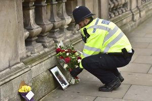 A police officer places flowers and a photo of fellow police officer Keith Palmer, who was killed in yesterday's attack on Whitehall near the Houses of Parliament in London, Thursday March 23, 2017. On Wednesday a knife-wielding man went on a deadly rampage, first driving a car into pedestrians then stabbing a police officer to death before being fatally shot by police within Parliament's grounds in London. (Dominic Lipinski/PA via AP)
