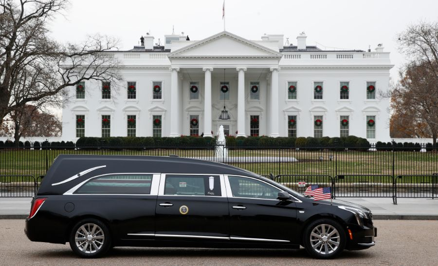 The hearse carrying the flag-draped casket of former President George H.W. Bush passes by the White House from the Capitol, heading to a State Funeral at the National Cathedral, Wednesday, Dec. 5, 2018, in Washington.
