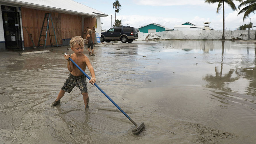 A child plays at his family's flooded gas station in the heavily damaged town of Everglades City the day after Hurricane Irma swept through the area on September 11, 2017 in Everglades City, Florida.