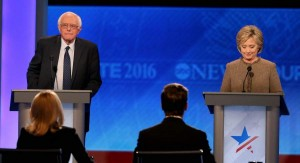 In this Dec. 19, 2015, file photo, then-Democratic presidential candidates Bernie Sanders and Hillary Clinton takes the stage for the debate at Saint Anselm College in Manchester, New Hampshire.