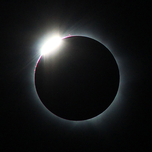 "One of the most beautiful sights associated with a total solar eclipse is the ""diamond ring."" It appears just before the beginning of totality, when a single bright point of sunlight — the diamond — shines through a deep valley on the Moon's limb (edge) and the inner corona — the ring — becomes visible. As the diamond vanishes, it's safe to remove your solar filters. A second diamond ring appears at the end of totality when a deep valley on the opposite side of the retreating Moon exposes a single bead of bright sunlight that begins to wash out the corona. Put your filters back on!"