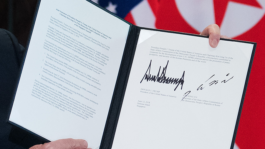 Close up of US President Donald Trump holding up a document signed by him and North Korea's leader Kim Jong Un following the signing ceremony.