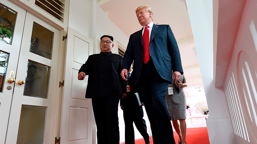 North Korea's leader Kim Jong Un (L) walks with US President Donald Trump (R) at the start of their historic US-North Korea summit in Singapore.