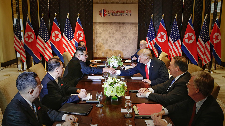 North Korean leader Kim Jong-un (L) shakes hands with U.S. President Donald Trump across the table in a meeting during their historic U.S.-DPRK summit in Singapore.