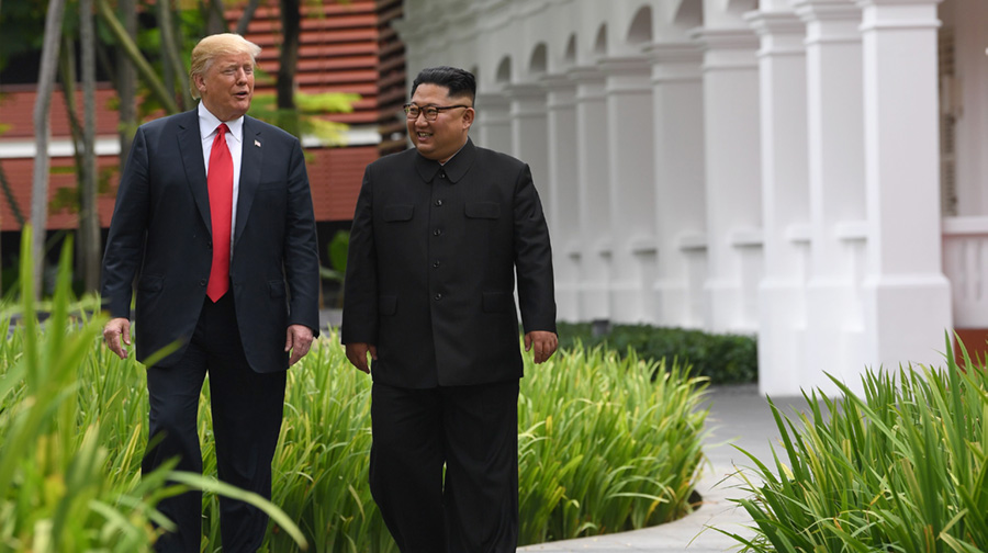 North Korea's leader Kim Jong Un (R) walks with US President Donald Trump (L) during a break in talks at their historic US-North Korea summit in Singapore.
