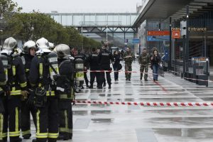Police officers, rescue workers, left, and soldiers patrol outside the Orly airport , south of Paris, Saturday, March, 18, 2017. A man was shot dead after wrestling a soldier to the ground at Paris' Orly Airport and trying to take her rifle, officials said. No one else in the busy terminal was hurt, but thousands of travelers were evacuated and flights were diverted to the city's other airport.