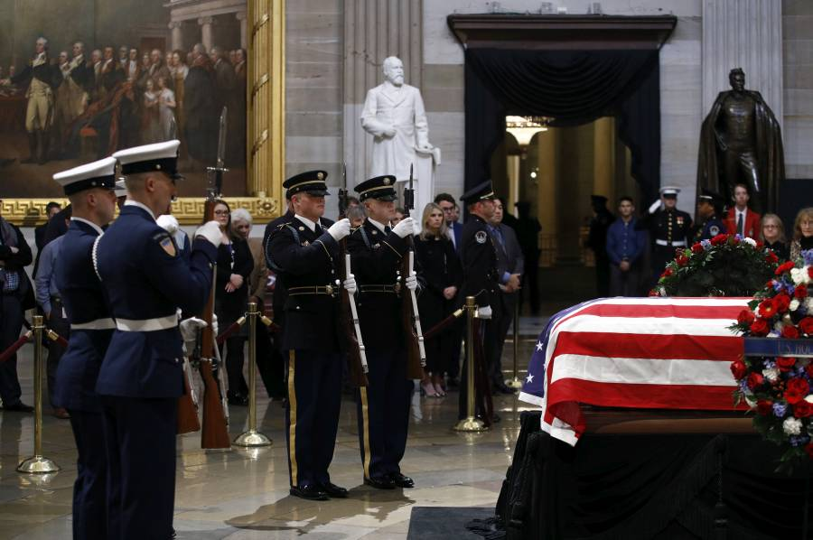 Service members perform a changing of the guard in front of the flag-draped casket of former President George H.W. Bush as he lie in state in the Capitol Rotunda in Washington, Tuesday, Dec. 4, 2018. (AP Photo/Patrick Semansky)