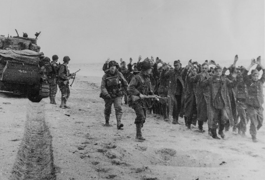 Original Caption: American soldiers march a group of German prisoners along a beachhead in Northern France after which they will be sent to England. June 6, 1944.