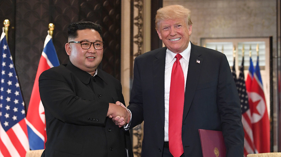 US President Donald Trump (R) and North Korea's leader Kim Jong Un shake hands following the signing ceremony.