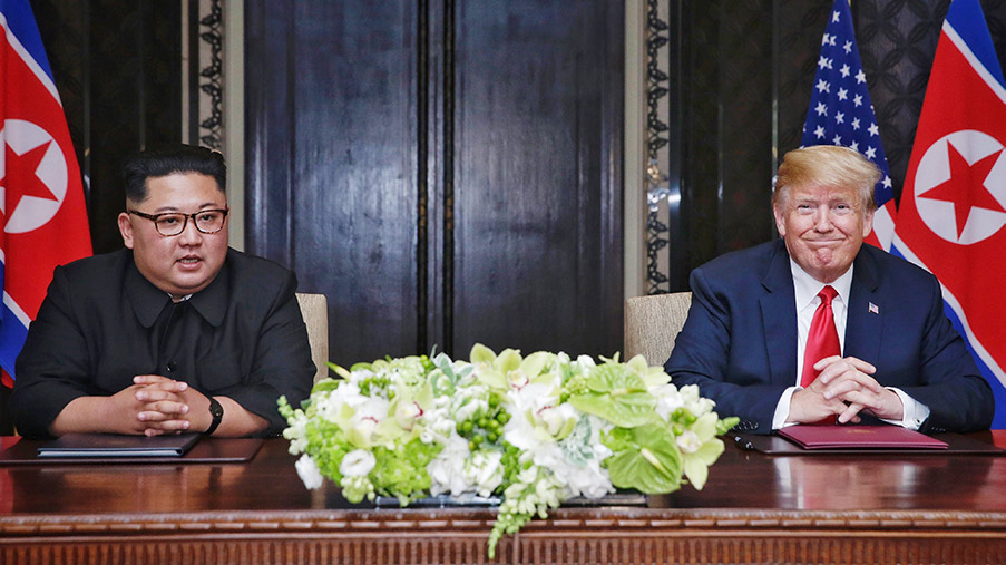 North Korean leader Kim Jong-un (L) sits down with U.S. President Donald Trump (R) to sign an agreement during their historic U.S.-DPRK summit in Singapore.