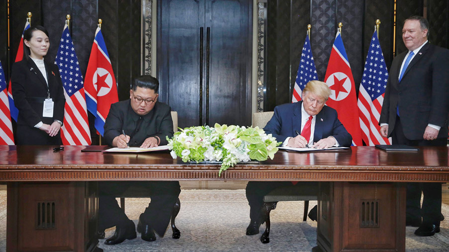 North Korean leader Kim Jong-un (L) and U.S. President Donald Trump (R) signing an agreement during their historic U.S.-DPRK summit in Singapore.