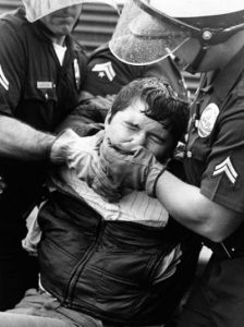 A pro-life demonstrator under assault by police in Los Angeles, 1989.