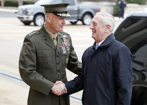 "FILE - In this Jan. 21, 2107 file photo, Joint Chiefs Chairman Gen. Joseph Dunford greets Defense Secretary Jim Mattis at the Pentagon. A new military strategy to meet President Donald Trump's demand ""to obliterate"" the Islamic State group is likely to deepen U.S. military involvement in Syria, possibly with more ground troops, even as the current U.S. approach in Iraq appears to be working and will require fewer changes. Dunford said Feb. 23 that the strategy will take aim not just at the Islamic State but at al-Qaida and other extremist organizations in the Middle East and beyond whose goal is to attack the United States. He emphasized that it would not rest mainly on military might. (AP Photo/Alex Brandon, File)"