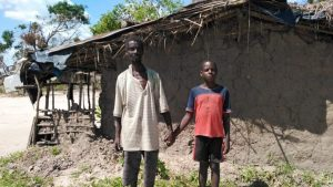 Two Mozambique men stand hand-in-hand outside a mud hut in the wake of Cyclone Idai.