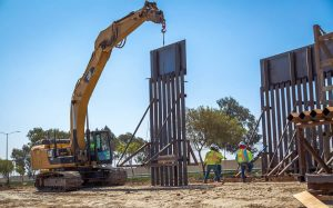 Construction Workers install a new section of the U.S.-Mexico border wall on June 19, 2018, in California.