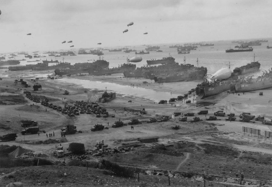 Original Caption: Supplies Pour Ashore for Invaders of France — This striking panorama of the French invasion beach was made by a Coast Guard combat photographer from a hillside cut with the trenchs (foreground) of the ousted Nazi defenders. The channel waters are black with shipping, as reinforcements and supplies are funneled ashore for the conquest of the Cherbourg Peninsula. Balloon barrages float overhead to protect the ships from low-flying enemy strafers. One balloon rests on the deck of an LST. Headed inland are long parades of trucks, loaded with troops and supplies.