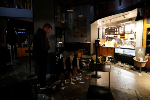 A worker surveys damage to a vandalized Starbucks after a protest turned violent at U.C. Berkeley over a scheduled speech by Milo Yiannopoulos in Berkeley, California.