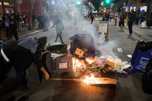 A demonstrator protesting Yiannopoulos sets a fire in Berkeley. (Photo: Noah Berger/EPA/Newscom)