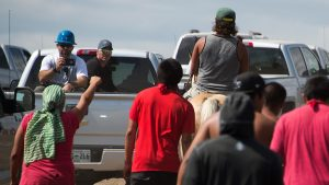 Private security guards in pick-up trucks drive away as Native Americans protestors and their supporters advance on land designated for the Dakota Access Pipeline (DAPL), after protestors confronted contractors and private security guards working on the oil pipeline project, forcing them to retreat, September 3, 2016, near Cannon Ball, North Dakota. Hundreds of Native American protestors and their supporters, who fear the Dakota Access Pipeline will polluted their water, forced construction workers and security forces to retreat and work to stop.