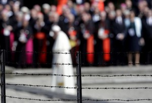 Pope Francis, background, is framed by a barbed wire as he prays in front of the Memorial at the former Nazi Death Camp Auschwitz-Birkenau, in Oswiecim, Poland, Friday, July 29, 2016. Pope Francis paid a somber visit to the Nazi German death camp of Auschwitz-Birkenau Friday, becoming the third consecutive pontiff to make the pilgrimage to the place where Adolf Hitler's forces killed more than 1 million people, most of them Jews. (AP Photo/Gregorio Borgia)