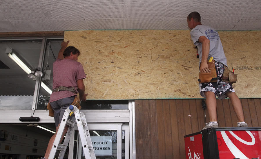 Robert Patch and John Courtney, of Local Builder's Construction, install wood paneling over windows at the Armstrong Grocery , Tuesday, Sept. 11, 2018, in New Bern, N.C., as storeowners and residents prepare for Hurricane Florence.