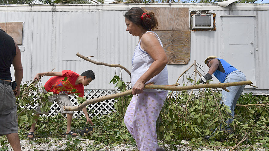 Marta Izaguirre, center, along with her neighbors pick up debris during clean-up efforts from Hurricane Irma in the Royal Duke Trailer Park on September 11, 2017 in Miami, Fl.