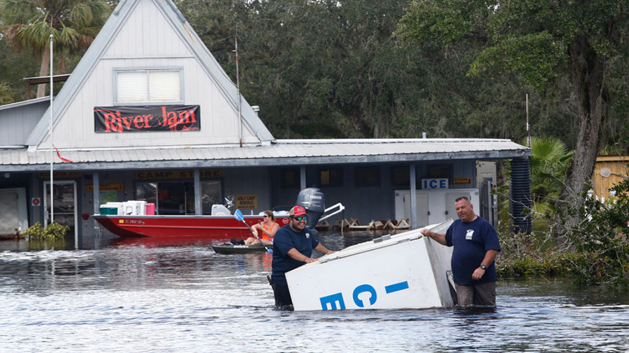 A crew works to salvage items, including an ice machine, as water from the nearby Peace River floods the Peace River Campground in the wake of Hurricane Irma on September 12, 2017 in Arcadia, Florida.