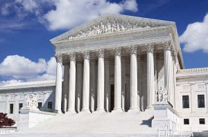 "Front facade of the U.S. Supreme Court building in Washington DC.  Words ""EQUAL JUSTICE UNDER LAW"" are clearly visible right above the columns. Vivid blue sky with clouds is in background."