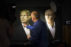 FILE - In this Wednesday, Nov. 9, 2016, file photo, a journalist points at a portrait of U.S. President-elect Donald Trump, with a portrait of Russian President Vladimir Putin during a live telecast of the U.S. presidential election in the Union Jack pub in Moscow, Russia. Putin's spokesman Peskov said Thursday that one way Trump could help build confidence with Russia after he becomes president would be to persuade NATO to slow down its expansion or withdraw its forces from Russia's borders. (AP Photo/Alexander Zemlianichenko, File)