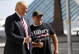 Mike Schuetz, A U.S. Marine veteran and owner of Hawkins Guns, in Hawkins, Wis., poses for photos with Republican Presidential candidate Donald Trump, left, at the Milwaukee County War Memorial Center in Milwaukee, Wis., Tuesday, Aug. 16, 2016. (AP Photo/Gerald Herbert)